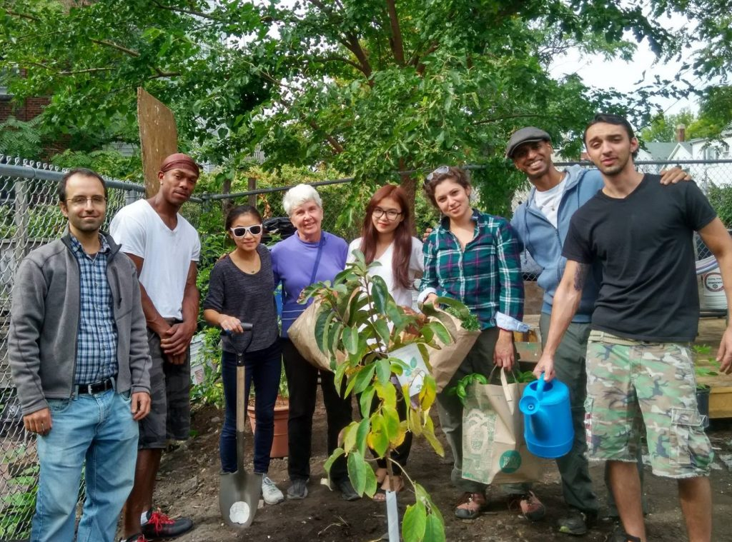 Kannan and a group of volunteers planting a persimmon tree at Eastie Farm